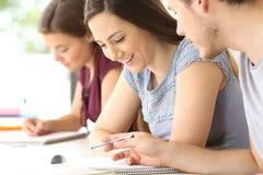 Studenten, die über Klassenarbeit am Klassenzimmer sprechen stockfotografie