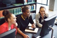 Studenten die aan computer in een universiteitsbibliotheek werken stock afbeelding