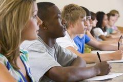 Studenten die aan een universitaire lezing luisteren stock afbeeldingen
