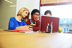 Studenten die aan laptop samenwerken Stock Foto's