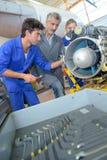 Studenten die aan vliegtuigenturbine werken stock foto's