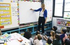 Studenten, die auf dem Boden hört auf Lehrer sitzen Stockbilder