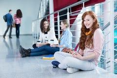 Studenten, die auf dem Boden sitzen Lizenzfreie Stockfotografie