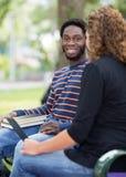 Studenten, die auf dem Campus auf Universität sitzen Stockbilder