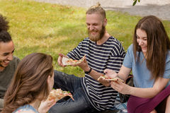 Studenten, die auf dem essenden und studierenden Rasen sitzen Stockbilder