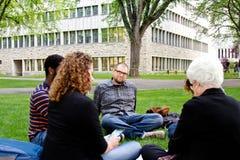 Studenten, die auf dem Grasbesuchen sitzen Lizenzfreies Stockfoto