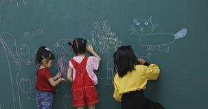 Studenten, die auf grünes Brett zeichnen stock video