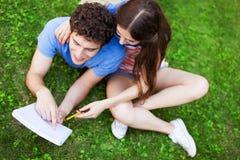 Studenten, die auf Gras sitzen Stockfotografie