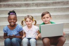 Studenten, die auf Schritten sitzen und eine Tablette und einen Laptop verwenden Stockbild