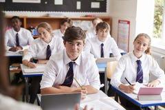 Studenten, die auf weiblichen Lehrer In Classroom hören stockbilder