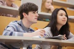 Studenten, die Aufmerksamkeit beim Sitzen in einem Vorlesungssal zahlen Stockbilder