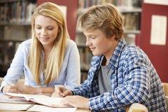2 studenten die in bibliotheek samenwerken Stock Foto's