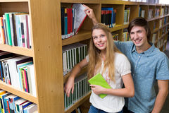 Studenten die bij camera in de bibliotheek glimlachen Stock Foto