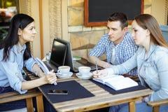 Studenten die bij koffie na les communiceren royalty-vrije stock afbeelding