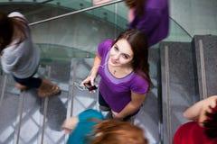 Studenten die boven en beneden een bezige trap meeslepen Stock Afbeeldingen