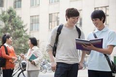 Studenten, die das Buch, einen anderen Studenten spricht mit Professor auf dem Hintergrund besprechen und betrachten Lizenzfreie Stockfotos