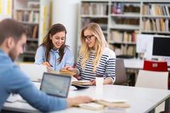 Studenten die in de bibliotheek bij campus werken Stock Foto