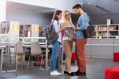 Studenten die in de bibliotheek bij campus werken Stock Foto's