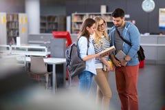 Studenten die in de bibliotheek bij campus werken Stock Afbeeldingen