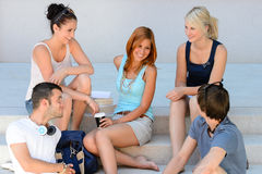 Studenten, die den Bruch sitzt auf Schulschritten genießen Stockfotografie