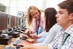 Studenten, die an den Computern in der Bibliothek mit Lehrer arbeiten Lizenzfreie Stockfotos