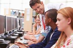 Studenten, die an den Computern in der Bibliothek mit Lehrer arbeiten Lizenzfreie Stockbilder