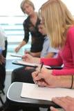Studenten, die an den Schreibtischen sitzen Lizenzfreies Stockbild