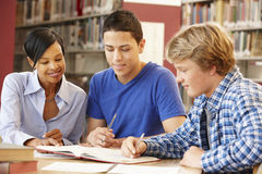 2 Studenten, die in der Bibliothek mit Lehrer arbeiten Lizenzfreie Stockfotos