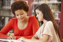 2 Studenten, die in der Bibliothek zusammenarbeiten Stockfotografie