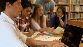 Studenten, die in der Bibliothek zusammenarbeiten stock video