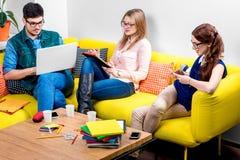 Studenten, die an der Couch arbeiten Lizenzfreie Stockfotos