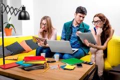 Studenten, die an der Couch arbeiten Stockbilder
