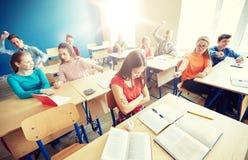 Studenten, die in der Schule hinter Mitschülerrückseite klatschen lizenzfreies stockfoto