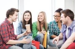 Studenten, die in der Schule in Verbindung stehen und lachen Lizenzfreie Stockfotos