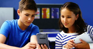 Studenten die digitale tablet en mobiele telefoon in klaslokaal met behulp van stock video