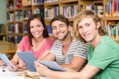 Studenten die digitale tabletten in bibliotheek gebruiken royalty-vrije stock afbeelding