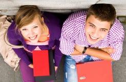 Studenten die door de muur zitten Stock Foto