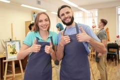 Studenten die duim-op gebaar in kunstacademie tonen stock foto's