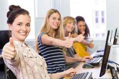 Studenten die duimen omhoog in computerklasse gesturing Stock Foto's