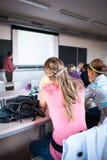 Studenten die in een klaslokaal tijdens klasse zitten royalty-vrije stock afbeeldingen