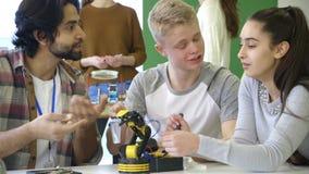 Studenten, die einen Roboterarm errichten stock footage