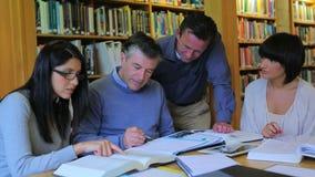 Studenten die elkaar in de bibliotheek helpen stock footage