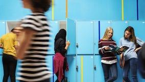 Studenten die en door de kasten koelen lopen stock foto's
