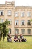 Studenten die en zitting op gras glimlachen spreken Royalty-vrije Stock Afbeeldingen