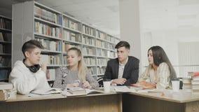 Studenten, die für Prüfungen beim an der Universitätsbibliothek bei Tisch sitzen zusammen sich vorbereiten bearbeiten stock footage