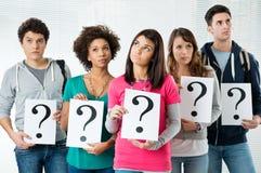 Studenten, die Fragezeichen anhalten Stockfoto