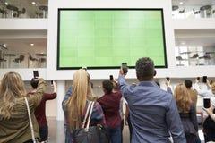 Studenten, die Großleinwand mit Telefonen, hintere Ansicht fotografieren Stockfotografie