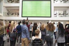 Studenten, die Großleinwand mit Telefonen, hintere Ansicht fotografieren Lizenzfreies Stockbild