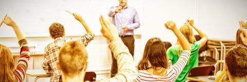 Studenten, die Hände im Klassenzimmer anheben stockbilder