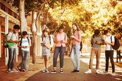 Studenten, die Handy auf Straße im Campus verwenden lizenzfreie stockbilder